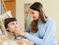 Girl caring for sick young man Royalty Free Stock Images
