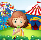 A girl at the carnival eating an icecream. Illustration of a girl at the carnival eating an icecream Royalty Free Stock Images