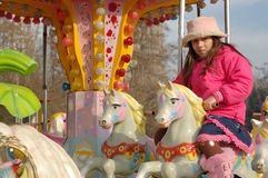 Girl on carousel. Young girl riding a carousel at the fair Stock Images