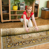 Girl and a carpet. The Image of the Girl spreading a carpet Royalty Free Stock Photo