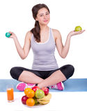 Girl on the carpet with apple and dumbbell Stock Photography