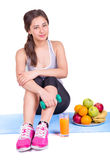 Girl on the carpet with dumbbell and fruit Stock Image