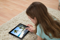 Girl On Carpet Looking At Digital Tablet Royalty Free Stock Photos