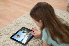Girl On Carpet Looking At Digital Tablet royalty free stock photos