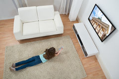 Girl On Carpet Watching Television. High Angle View Of Girl Lying On Carpet Watching Television At Home Stock Image