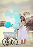 Girl and carriage. A birthday girl posing with a baby carriage with dozen of white and blue balloons Royalty Free Stock Photo