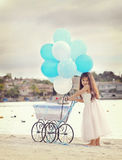Girl and carriage. A birthday girl posing with a baby carriage with dozen of white and blue balloons Stock Photo
