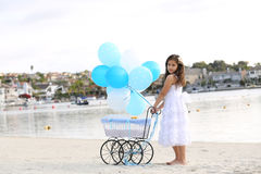 Girl and carriage. A birthday girl posing with a baby carriage with dozen of white and blue balloons Royalty Free Stock Images
