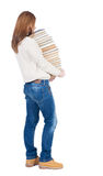 A girl carries a heavy pile of books. back view. Rear view peopl Royalty Free Stock Images