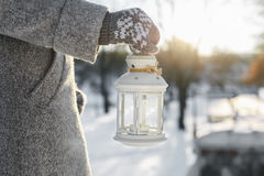 The girl carries lantern with a burning candle inside. Royalty Free Stock Photography