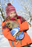 Girl carrying dog in snow. White child having fun with baby animal in winter season Stock Images