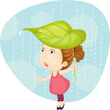 A Girl Carrying Leaf on Head Stock Image