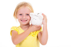Girl carrying piggybank Royalty Free Stock Image