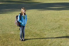Girl carrying school backpack. Smiling child (11 years) carrying bookbag over her shoulder, standing on grass Royalty Free Stock Photo