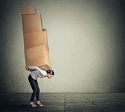 Girl carrying several boxes on her back in equilibrium Royalty Free Stock Photography