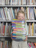 Girl Carrying Stack Of Books In Library Stock Photography