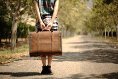 A girl carrying a suitcase on a pathway. Stock Photos