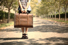 A girl carrying a suitcase on a pathway. Travel concept Stock Photos