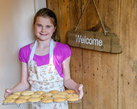 Girl carrying tray of cookies by a front door with welcome sign. Stock Image