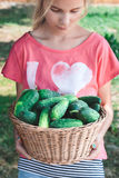 Girl carrying wicker basket with cucumbers Royalty Free Stock Photos