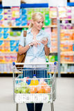 Girl with cart full of food in the market Stock Images