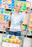 Girl with cart full of food in the store. Concept of consumerism, retail and purchase Royalty Free Stock Photo