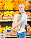 Girl with cart hands packet with fresh vegetables Stock Photos