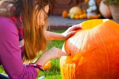 Girl carving jack-o-lantern. In autumn Stock Photo