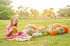 Girl carving and scooping pumpkin Stock Images