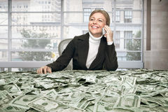 Girl with cash. Portrait of young woman sitting behind the table full of cash stock images