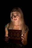 Girl with a casket. Portrait of blonde girl on a dark background in the hands of a casket Stock Photo