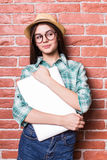 Girl in casual clothes, hat and eyeglasses posing,  smiling and with close laptop in hands Stock Images