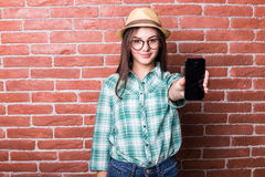 Girl in casual clothes, hat and eyeglasses posing, smiling and demonstrate on smartphone Stock Photography