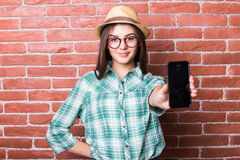 Girl in casual clothes, hat and eyeglasses posing, smiling and demonstrate on smartphone Royalty Free Stock Photos