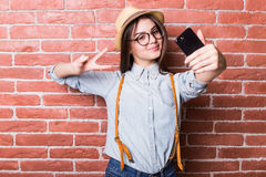 Girl in casual clothes and hat, eyeglasses, posing, smiling, making selfie Stock Photos