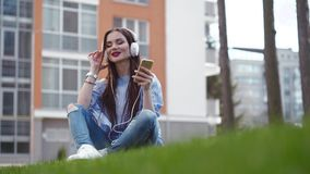 Girl in casual jeans, blue blouse, and white sneakers sits on the green grass and uses her phone for listening music stock footage