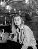 Girl in casual outfit sits in wooden vintage interior. Relax concept. Girl tomboy relax with glass with mulled wine in. House of gamekeeper. Lady on dreamy face royalty free stock photos