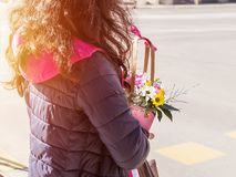 A girl in a casual purple jacket holding a small pink basket with flowers at a pedestrian crossing, rear view. Real people and city life on a sunny spring day stock images