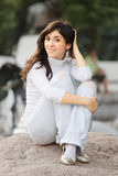 Girl in casual sitting on stone Stock Photos