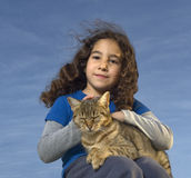Girl and cat. Little girl holding a cat against  blue sky Royalty Free Stock Image
