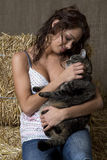 Girl and cat. Young women sitting on bales of her, holding her cat stock image