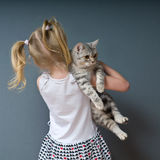 Girl and cat. A girl with blond hair stands with his back to us and is holding a cat Royalty Free Stock Photography