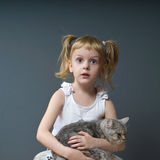 Girl and cat_3. A girl with blond hair is holding a cat and and looks at us Stock Photography