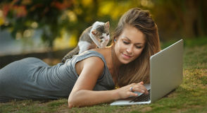 Girl and a cat on the grass watching laptop Royalty Free Stock Photos