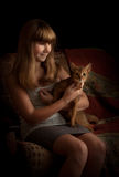 Girl with cat, indoors. Low key. Royalty Free Stock Images