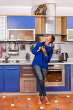 Girl and a cat in the kitchen. The kitchen in the apartment the girl in the blue jacket and a cat on the cabinet Royalty Free Stock Photo