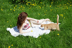 The girl with a cat lies on a  grass Stock Photo