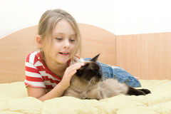 Girl with a cat lying on the bed. Little girl with a cat lying on the bed of yellow color Royalty Free Stock Photography