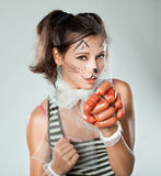 Girl with cat muzzle in his hand holding sausages. Royalty Free Stock Photo