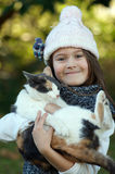 Girl with cat. Portrait of pretty little girl happily and tenderly holding her cat in a winter outdoor setting Royalty Free Stock Photo